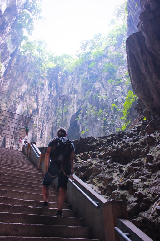 Homme marchant dans la la grotte principale de la Batu Caves