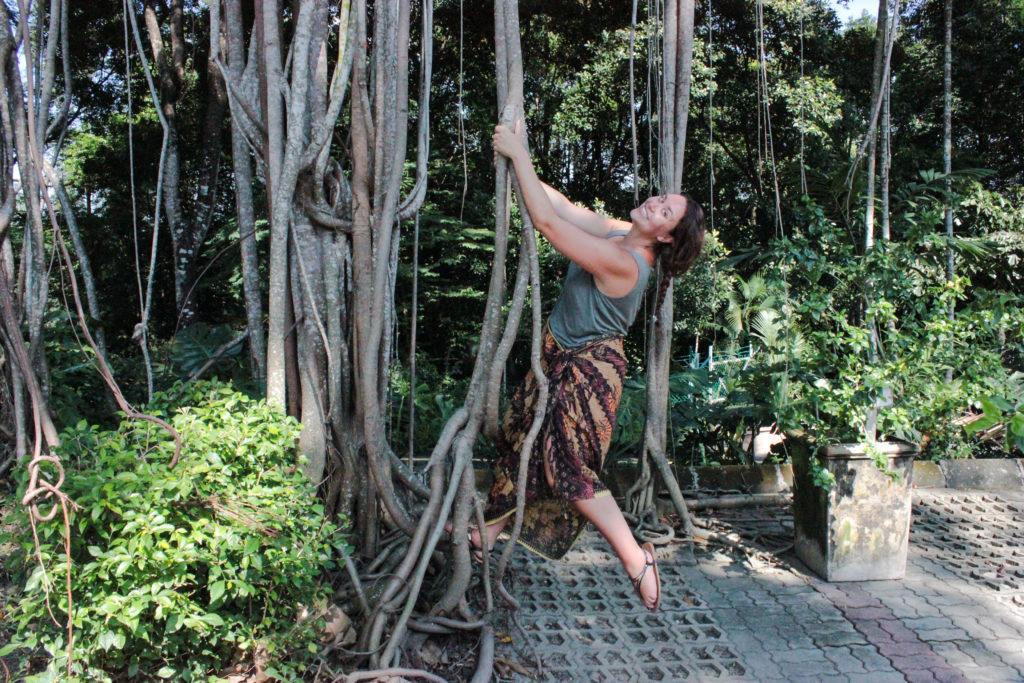 Image d'une femme qui se balance sur des lianes au Perdana Botical Garden