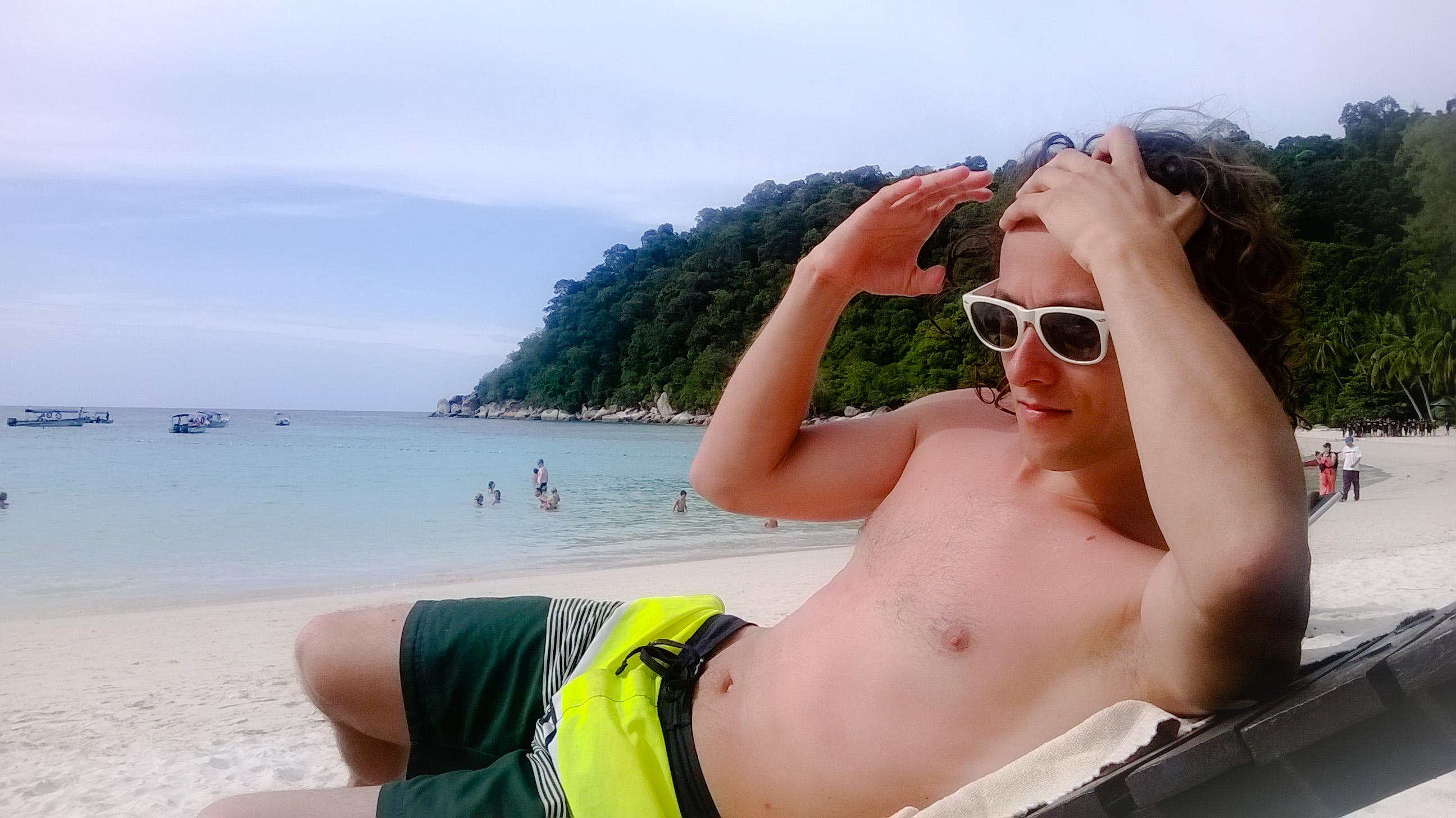 Image d'un homme allongé sur un transat sur la plage du Perhentian Island Resort