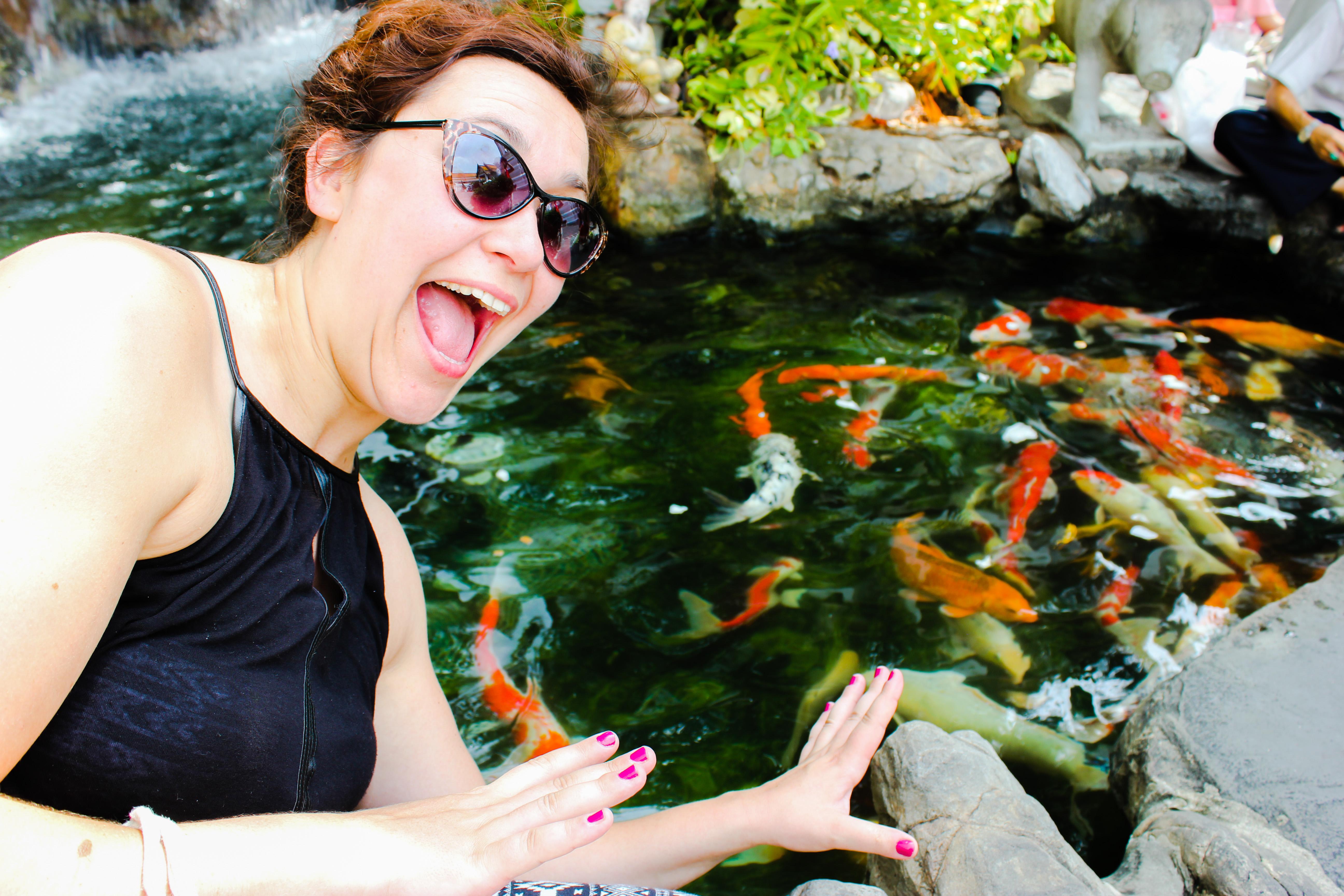 Image d'une femme devant un bassin de poisson au Temple du Bouddha d'or