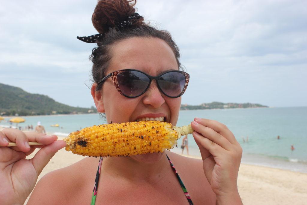 Image d'une femme qui mange un épi de maïs