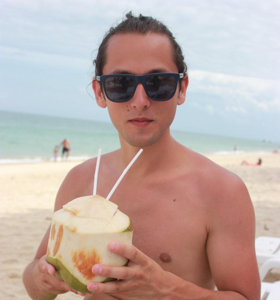 Image d'un homme qui boit une noix de coco
