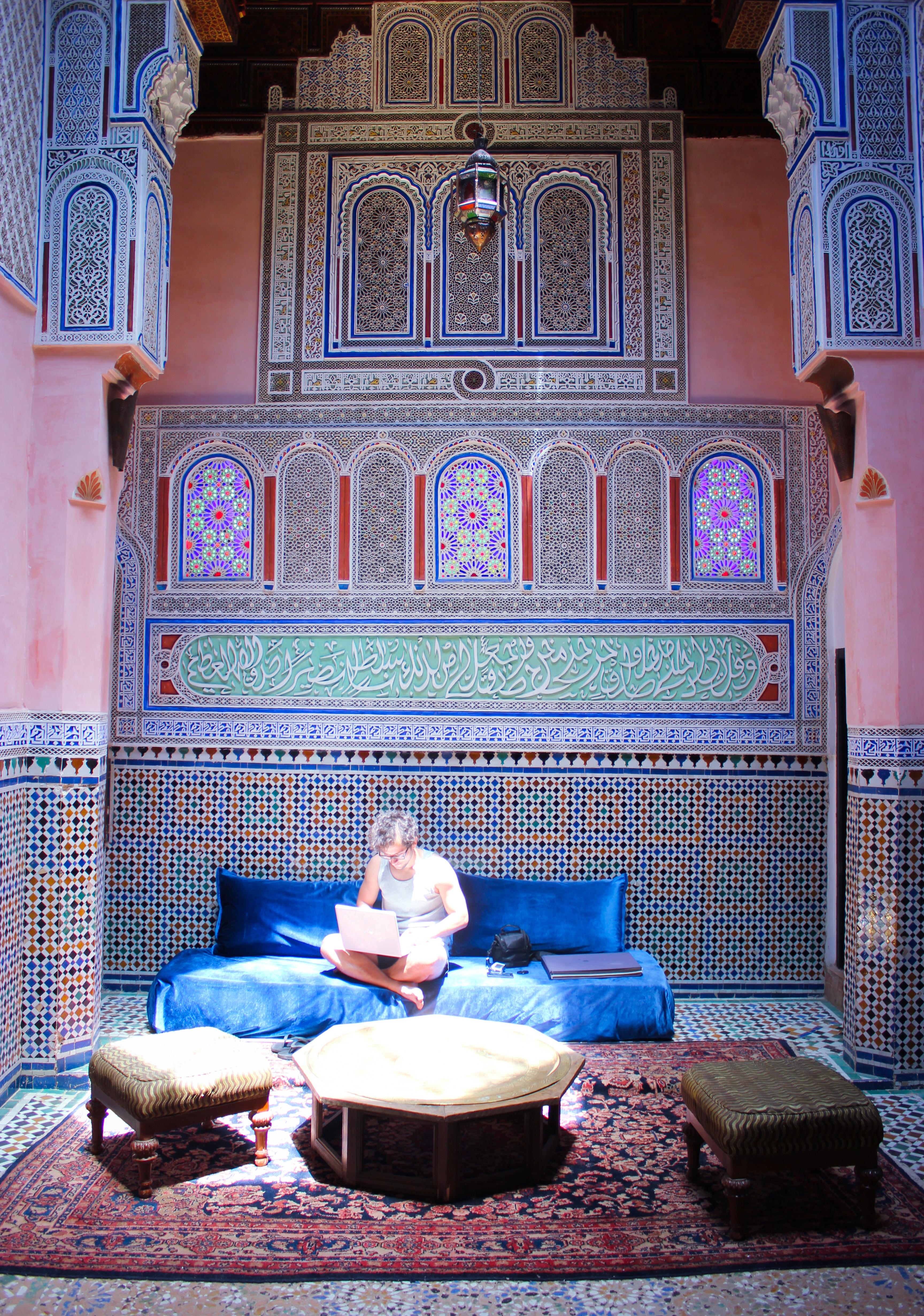 Un homme travaille sur son ordinateur dans le salon du riad d'or à Meknès