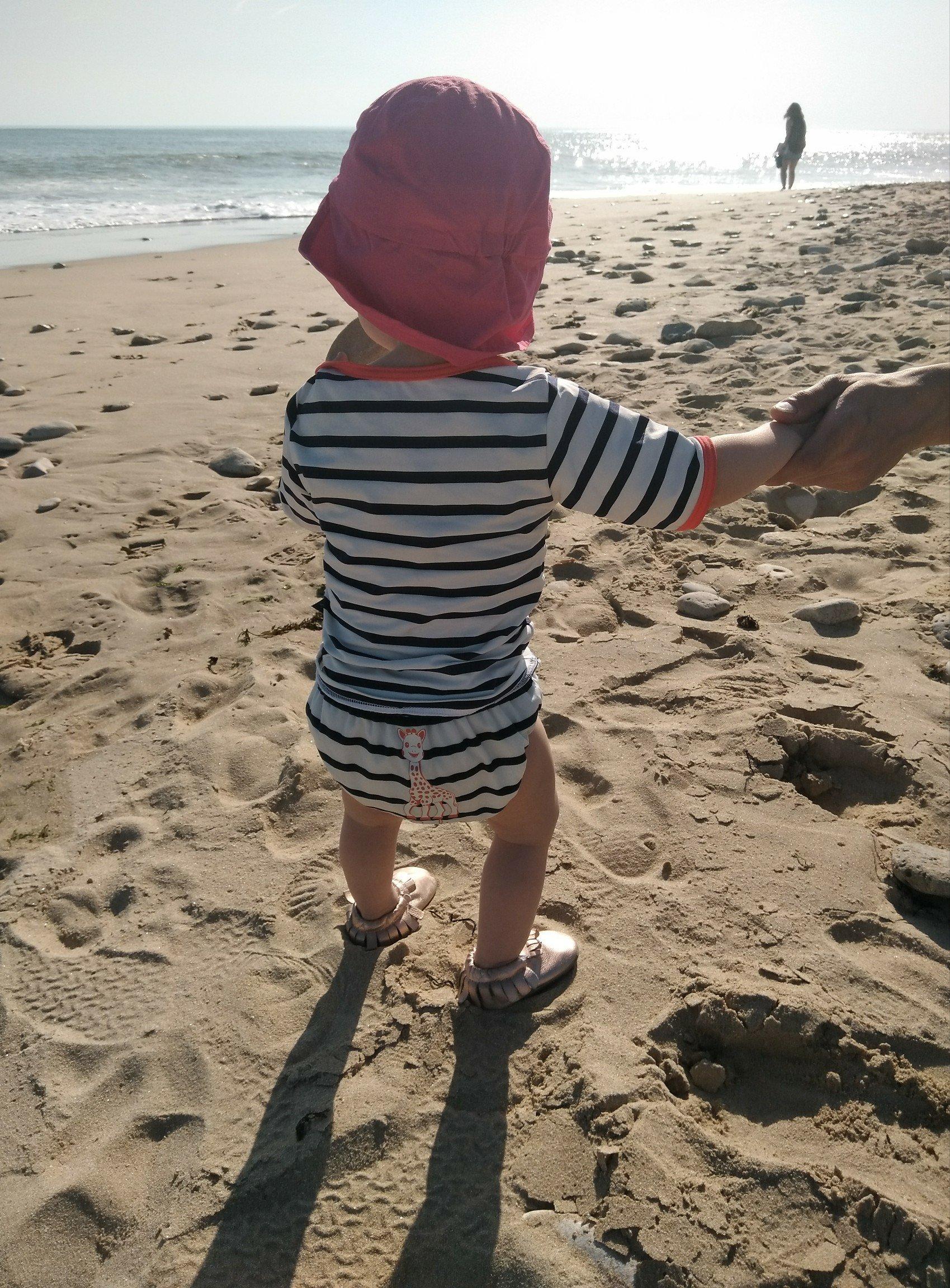 Bébé regarde la mer et porte un maillot de bain anti-UV MAYOPARASOL